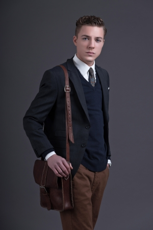 Retro fifties fashion young businessman wearing dark suit and tie. Holding a brown leather bag. Studio shot against grey. photo
