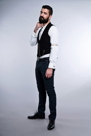 Retro hipster 1900 fashion man with black hair and beard. Studio shot against grey. Stock Photo - 25226857