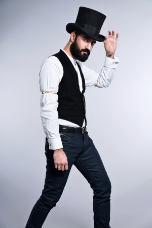 Retro hipster 1900 fashion man with black hair and beard. Wearing black hat. Studio shot against grey. photo