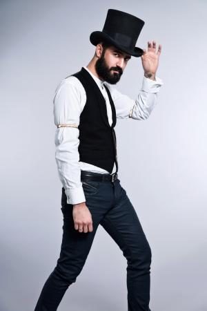 beard: Retro hipster 1900 fashion man with black hair and beard. Wearing black hat. Studio shot against grey.
