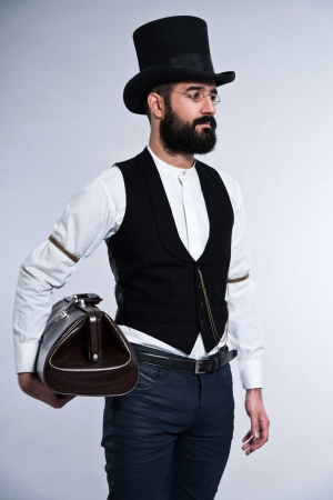 Retro hipster 1900 fashion man with black hair and beard. Wearing black hat. Holding vintage bag. Studio shot against grey. photo