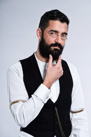 Retro hipster 1900 fashion man with black hair and beard. Wearing vintage glasses. Studio shot against grey. photo