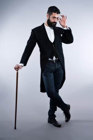 Retro hipster 1900 fashion man with black hair and beard. Standing with walking cane. Wearing vintage glasses. Studio shot against grey. Stock Photo