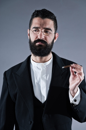 Retro hipster 1900 fashion man with black hair and beard. Smoking cigar. Wearing vintage glasses. Studio shot against grey. photo