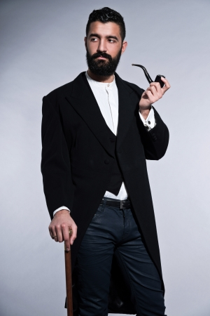 Retro hipster 1900 fashion man with black hair and beard. Smoking pipe. Studio shot against grey. photo