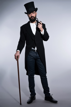 Retro hipster 1900 fashion man with black hair and beard. Wearing black hat. Standing with cane. Smoking pipe. Studio shot against grey. Stock Photo