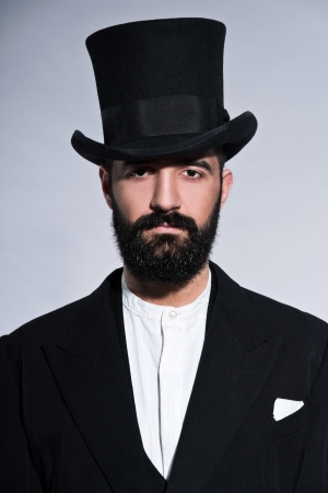 Retro hipster 1900 fashion man in suit with black hair and beard. Wearing black hat. Studio shot against grey. photo