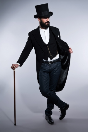 검은 머리와 수염을 가진 소송에서 레트로 힙 스터 1900 패션 남자. 검은 모자를 입고. 지팡이를 짚고 서. 스튜디오 회색에 대하여 총.