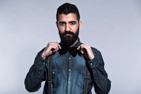 Retro hipster 1900 fashion man with black hair and beard. Wearing blue jeans shirt, bow tie. Studio shot against grey.
