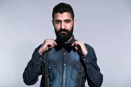 tie bow: Retro pantaloni a vita bassa 1900 di moda uomo con i capelli neri e la barba. Indossa jeans blu camicia, farfallino. Studio sparato contro grigio.