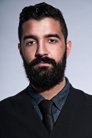 Retro hipster 1900 fashion man in suit with black hair and beard. Wearing gilet plus tie. Studio shot against grey. Stock Photo