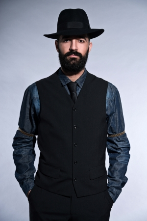 Retro hipster 1900 fashion man in suit with black hair and beard. Wearing gilet plus hat. Studio shot against grey.