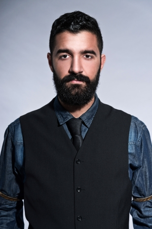Retro hipster 1900 fashion man in suit with black hair and beard. Wearing gilet plus tie. Studio shot against grey. Stockfoto