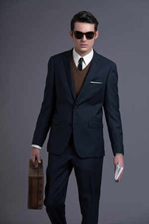 grease: Retro 50s business fashion man with dark grease hair. Wearing dark blue suit and sunglasses. Holding vintage suitcase. Studio shot against grey. Stock Photo