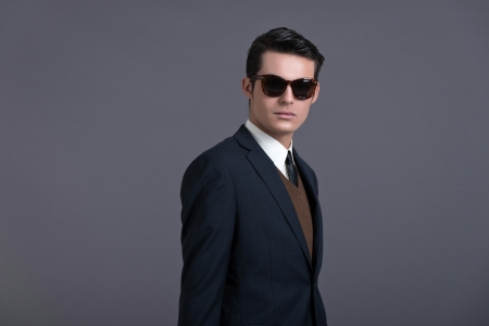 Retro 50s business fashion man with dark grease hair. Wearing dark blue suit and sunglasses. Studio shot against grey.