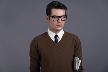 Retro fifties fashion man with dark grease hair. Wearing brown sweater with black tie and glasses. Holding newspaper. Studio shot against grey. photo