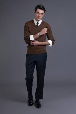englishman: Retro 1950s fashion man with dark grease hair. Wearing brown sweater with black tie. Studio shot against grey.
