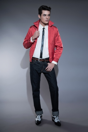 Retro rock and roll fifties fashion man with dark grease hair. Wearing red jacket and jeans. Studio shot against grey.