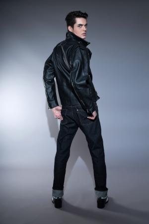 Retro rock and roll jaren '50 mode man met donker vet haar. Dragen zwart lederen jas en spijkerbroek. Studio shot tegen grijs.