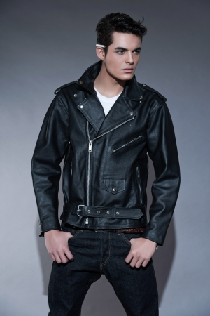 Retro rock and roll 50s fashion man with dark grease hair. Cigarette on his ear. Wearing black leather jacket. Studio shot against grey.