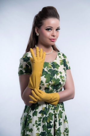 Retro fifties fashion housewife wearing yellow rubber gloves. Studio shot against grey. Stock Photo