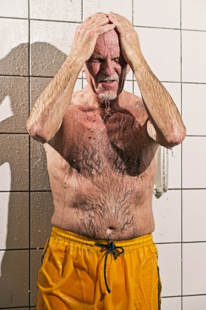 tomando refresco: Hombre mayor que toma una ducha en el baño. Vistiendo traje de baño amarillo. Foto de archivo