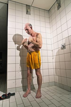 tomando refresco: Hombre mayor que toma una ducha en el ba�o. Vistiendo traje de ba�o amarillo. Foto de archivo