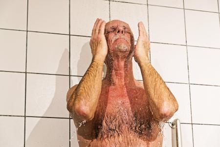 tomando refresco: Hombre mayor que toma una ducha en el ba�o. Foto de archivo
