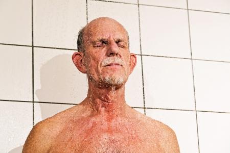 tomando refresco: Hombre mayor que toma una ducha en el baño. Foto de archivo