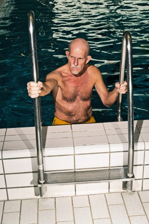 Senior man walking out of swimming pool. Wearing yellow swimming trunks. photo