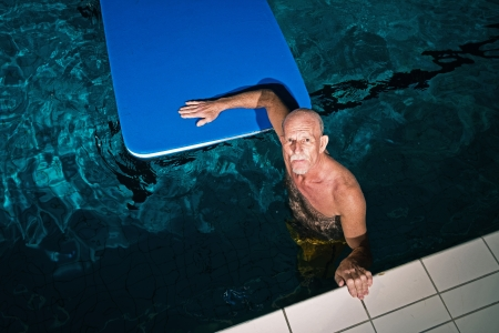 Healthy active senior man with beard in indoor swimming pool playing with foam raft. photo