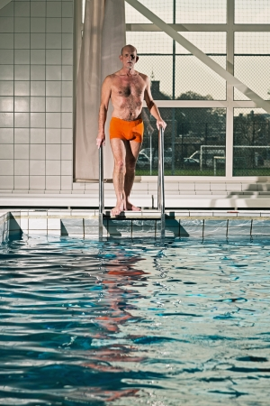 Healthy active senior man with beard in indoor swimming pool going in the water. Wearing orange swimming trunks. photo