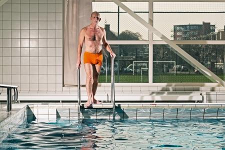 going in: Hombre Mayor activo sano con barba en la piscina cubierta de ir en el agua. El uso de traje de ba�o de color naranja.