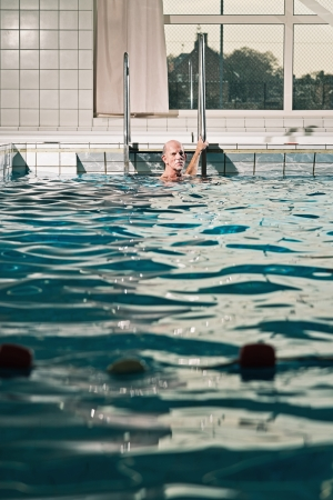 Healthy active senior man with beard in indoor swimming pool. photo