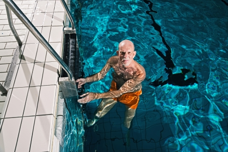 Healthy active senior man with beard in indoor swimming pool. Wearing orange swimming trunks. photo