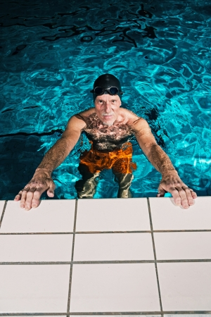 Active healthy senior man with beard in swimming pool wearing black cap and glasses. photo