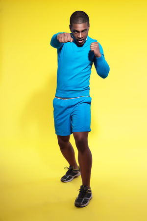 Athletic black man in sportswear fashion. Boxer. Intense colors. Studio shot against yellow. photo
