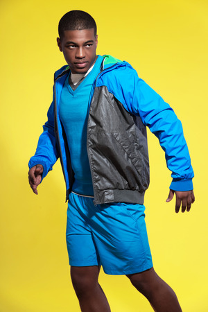 Athletic black man in sportswear fashion. Runner with jacket. Intense colors. Studio shot against yellow. photo