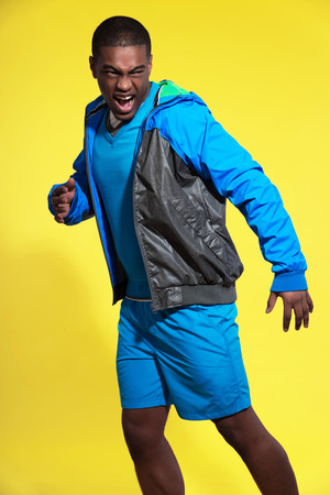 Screaming athletic black man in sportswear fashion. Runner with jacket. Intense colors. Studio shot against yellow. photo