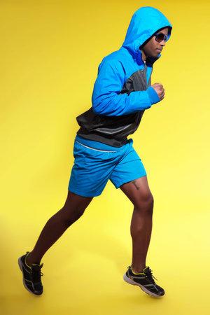 hoody: Спортивное черный человек в спортивной моде. Бегун с капюшоном куртки и солнцезащитные очки. Насыщенные цвета. Студия выстрел против желтой.