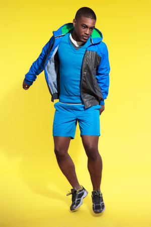 Jumping athletic black man in sportswear fashion. Runner with hoody jacket. Intense colors. Studio shot against yellow. photo