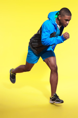 hoody: Прыжки атлетические черный человек в спортивной моде. Бегун с капюшоном куртки. Насыщенные цвета. Студия выстрел против желтой.