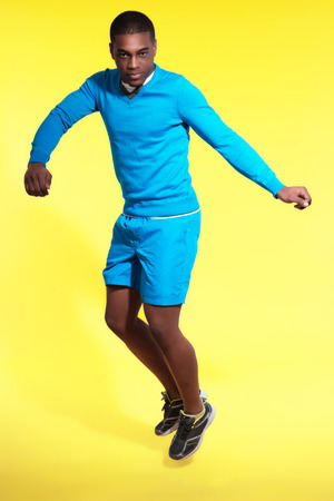 Jumping athletic black man in sportswear fashion. Wearing blue shirt and shorts. Intense colors. Studio shot against yellow. photo