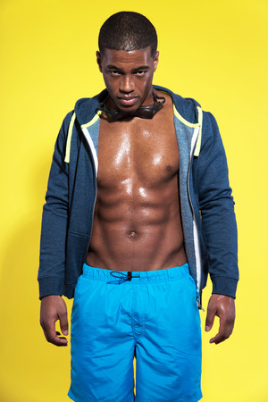 Athletic swimmer with waterdrops. Black man in sportswear fashion. Wearing sweater. Intense colors. Studio shot against yellow. photo