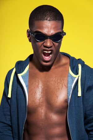 Screaming athletic swimmer with waterdrops. Black man in sportswear fashion. Wearing protective glasses. Intense colors. Studio shot against yellow. photo
