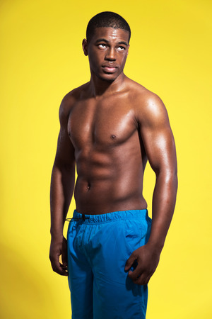 Athletic swimmer with waterdrops. Black man wearing blue swimming shorts. Intense colors. Studio shot against yellow. photo