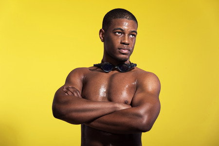 Athletic swimmer with waterdrops. Black man with protective glasses. Intense colors. Studio shot against yellow. photo
