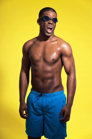 Athletic swimmer with waterdrops. Black man wearing blue swimming shorts and protective glasses. Intense colors. Studio shot against yellow. photo
