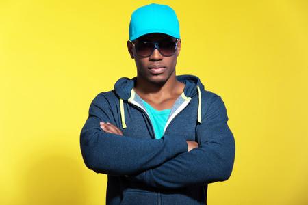 青いスポーツウェアのファッションを着てサングラス アスレチック ランナー。黒人男性。ブルーのキャップとセーター。強烈な色。黄色の背景に対 写真素材