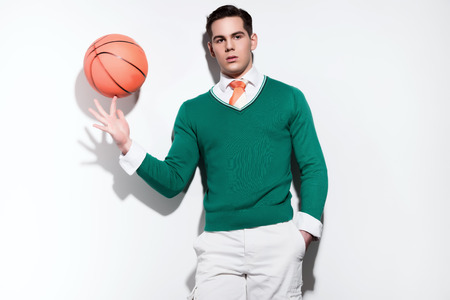Retro basketball fashion man wearing a green sweater orange tie and white shorts. Studio shot against white wall. photo